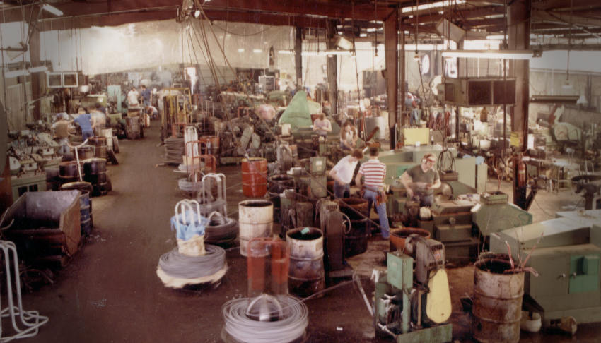 Photo of Whitesell Manufacturing in Muscle Shoals Alabama showing manufacturing floor. This photo is circa 1984. A young Neil Whitesell can be seen near center bending to look at a machine set up.