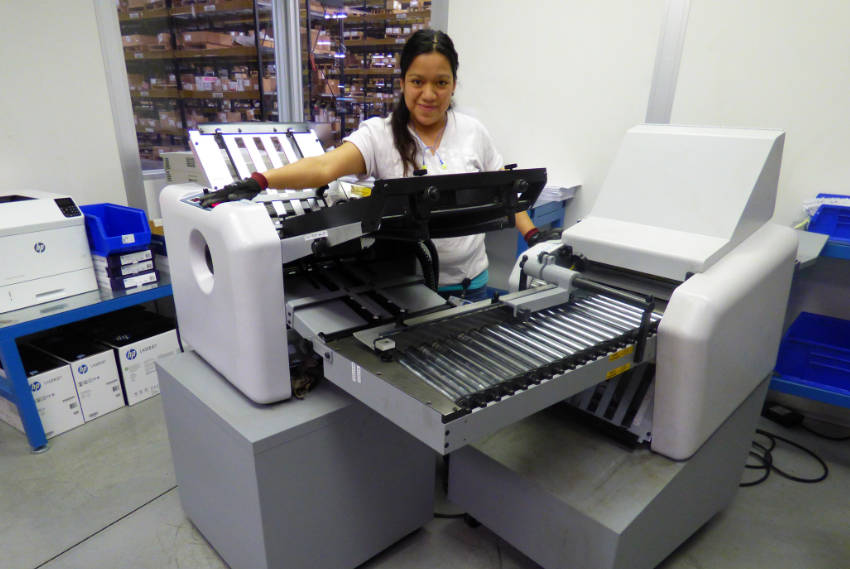 Photo shows operator at bulk printing station where User Manuals and other materials are printed for inclusion in completed assemblies.